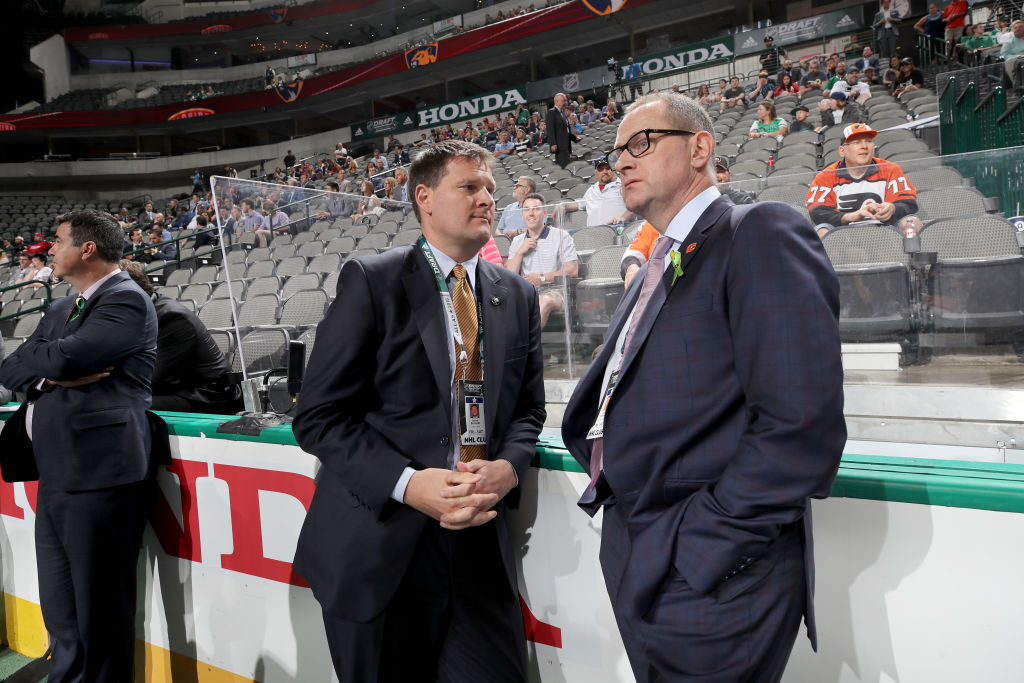 Sabres GM Jason Botterill, left, talks to Calgary's Brad Treliving on Saturday in Dallas (Getty Images).