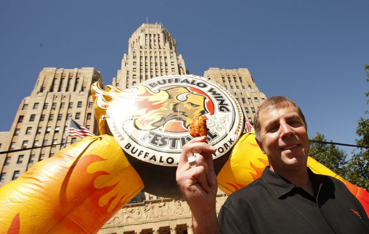 'Wing King' Drew Cerza holds up a 'jumbo' chicken wing during a news conference promoting the 11th annual National Buffalo Wing Festival in 2012. Cerza is holding a National Blue Cheese Day on July 16.  (News file photo)