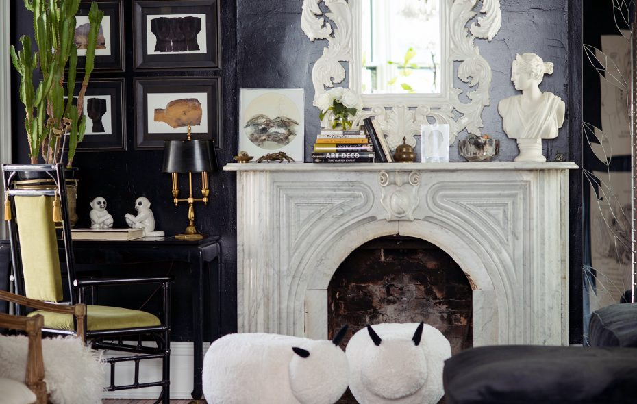 """A fireplace bought in pieces on Craigslist adds warmth to the calming """"hangout"""" room where Fineberg eats dinner most nights. To the left is a series of Belgian prints from Etsy. (Katie Ambrose)"""