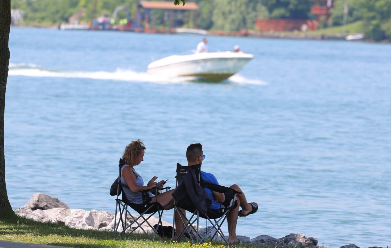 Linda Cutler, left,  and her son Jared both from Amherst, sit in the shade and watch as boats go by at Niawanda Park, in the City of Tonawanda. (John Hickey/Buffalo News)