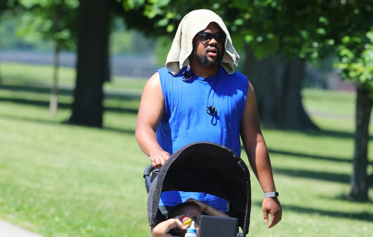 Antwon Smith tries to stay cool with a wet towel on his head as he takes his son Cameron, 4, out for a stroll in Delaware Park.   (John Hickey/Buffalo News)