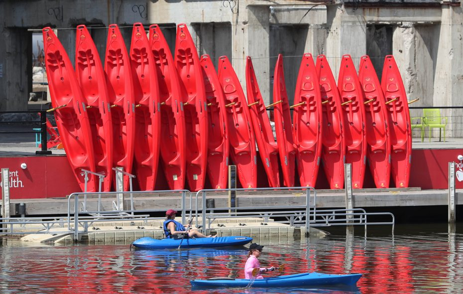 Kayakers ride past kayaks stored at RiverWorks, one of the hot spots for outdoor summer fitness on the Buffalo waterfront. (Sharon Cantillon/Buffalo News)