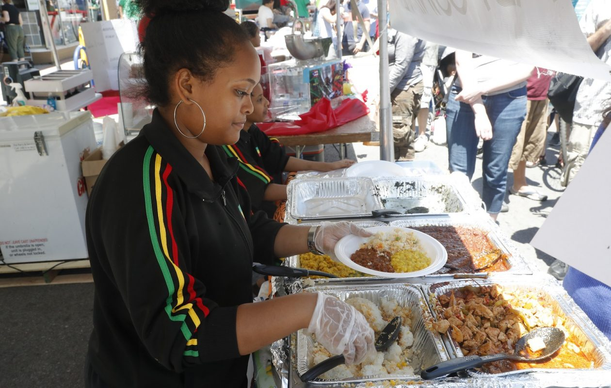 Feben Tesfaye serves food at Abyssinia Ethiopian's tent at the 2017 Taste of Diversity. (John Hickey/News file photo)