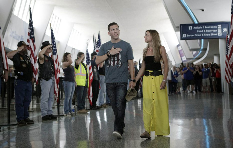 Maj. Patrick Miller and his wife, Ashley, walk through a row of Patriot Guard Riders and supporters during a visit home in 2014. (Derek Gee/News file photo)