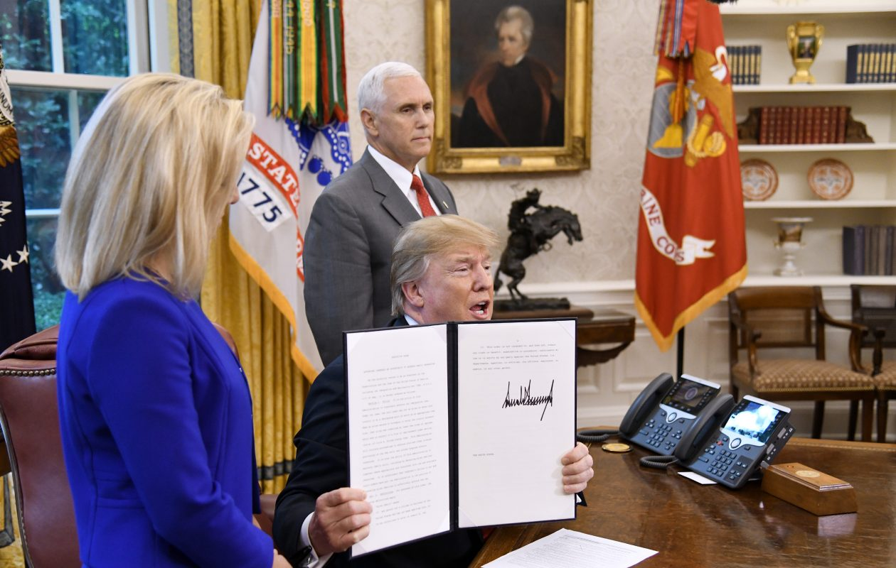 President Donald Trump holds a signed executive order to keep families together at the border in the Oval Office of the White House on June 20, 2018. (Olivier Douliery/Abaca Press/TNS)
