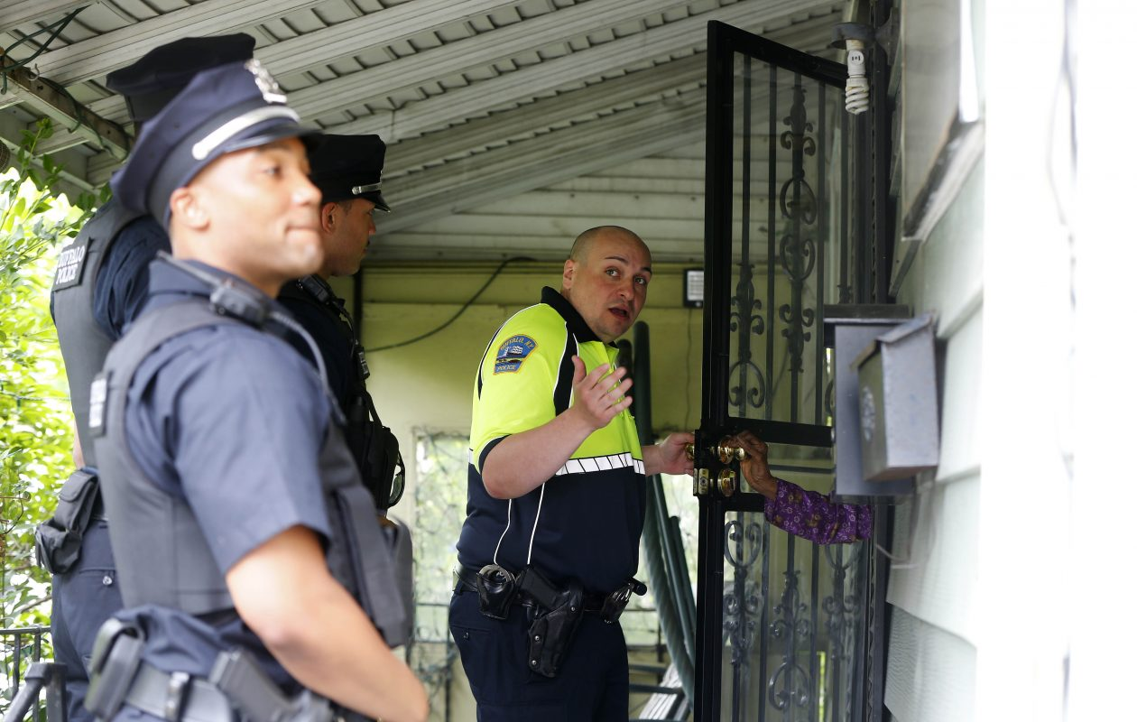 Buffalo Police Officer Santino Tomasula speaks with a resident on Bissell Avenue on the first day of the Operation Clean Sweep program in Buffalo Wednesday, June 20, 2018. The sweeps are being done throughout the city in conjunction with the Buffalo Police Commissioner's Neighborhood Engagement Team initiative. (Mark Mulville/Buffalo News)