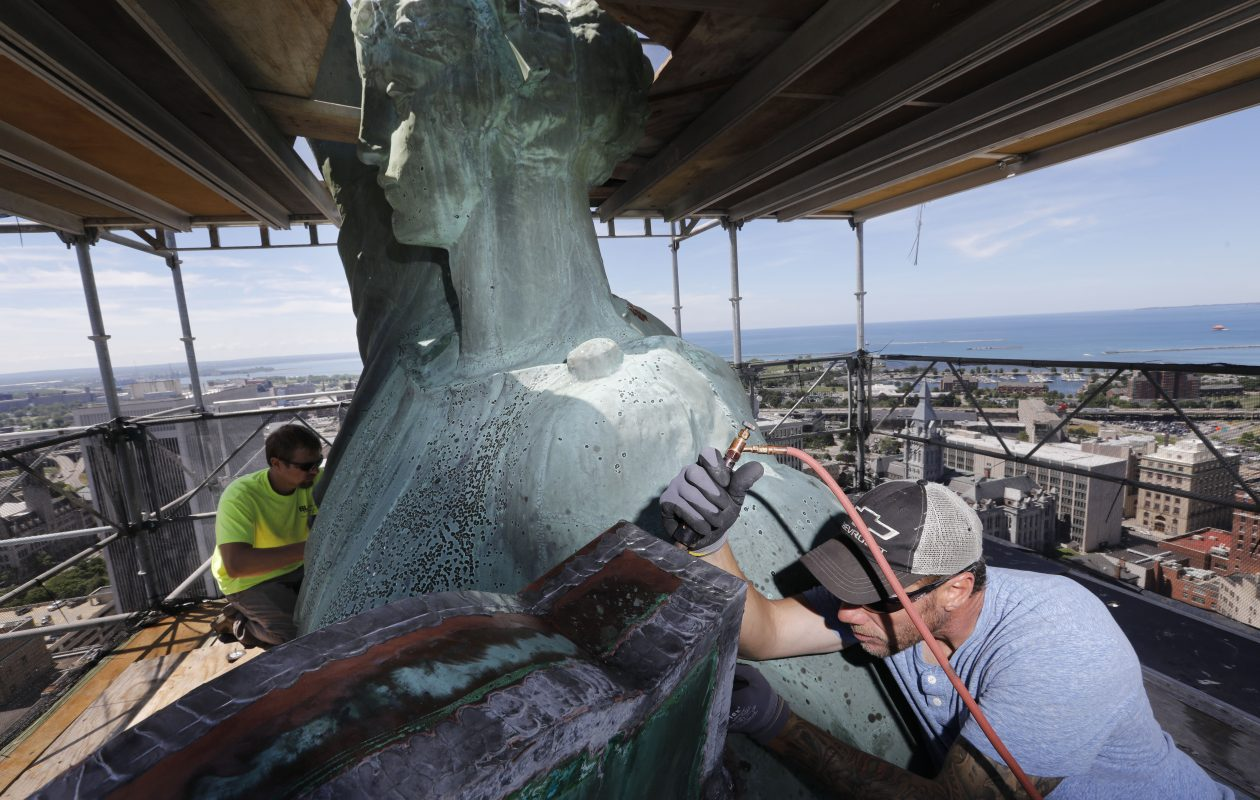 James Carpino, right, a union sheet metal foreman at Local 71, and fifth-year apprentice Matt Strojny, left, at work high above the city on a recent summer day. (Derek Gee/Buffalo News)