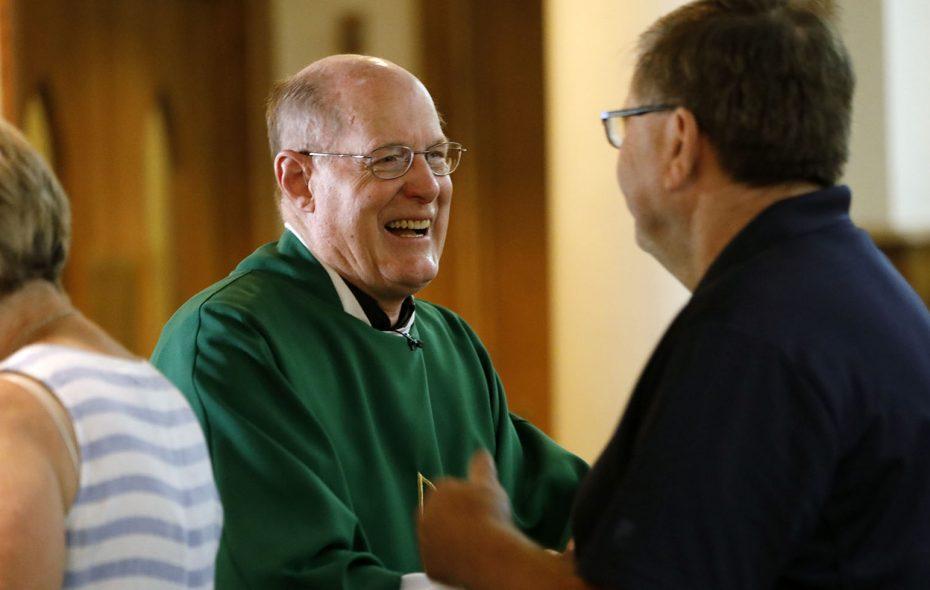 The Rev. Dennis Riter, pastor of St. Elizabeth Ann Seton Catholic Church in Dunkirk, greets parishioners following Mass on Sunday morning. (Derek Gee/Buffalo News)
