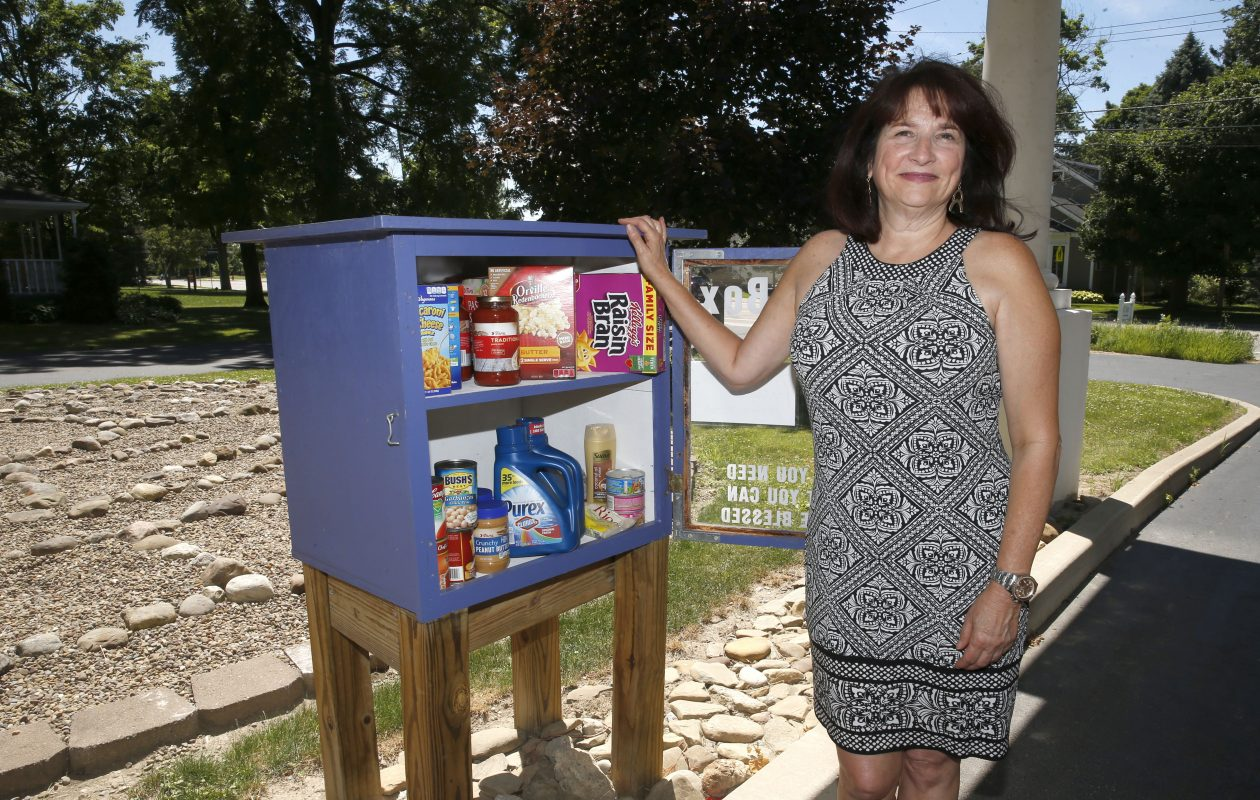 Michele Pellette makes sure that there's plenty of food in the Blessing Box at Orchard Park Presybyterian Church. (Robert Kirkham/Buffalo News)