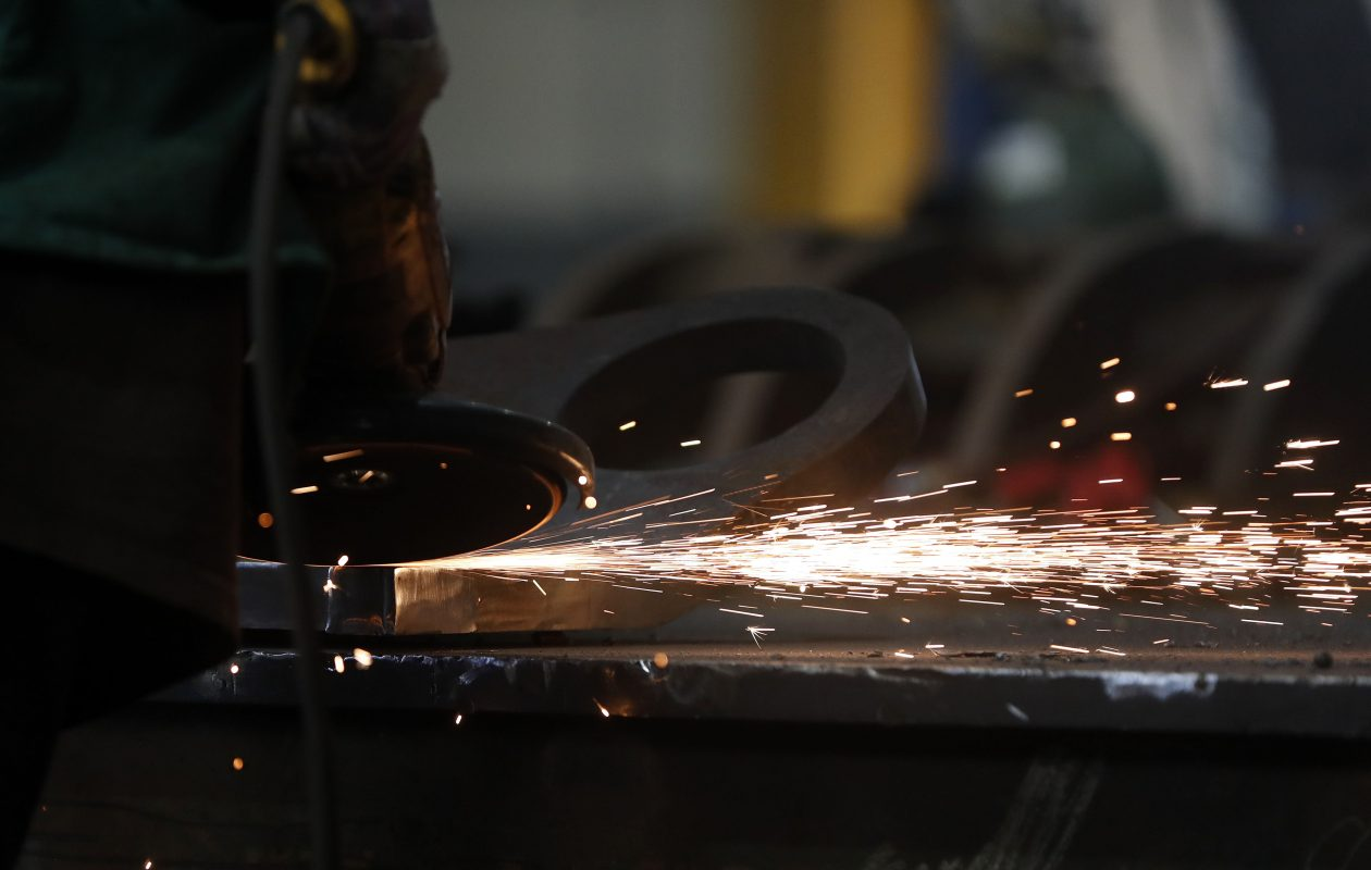 A worker at OSC Holdings, Inc grinds metal at the facility in Buffalo. (Mark Mulville/Buffalo News)