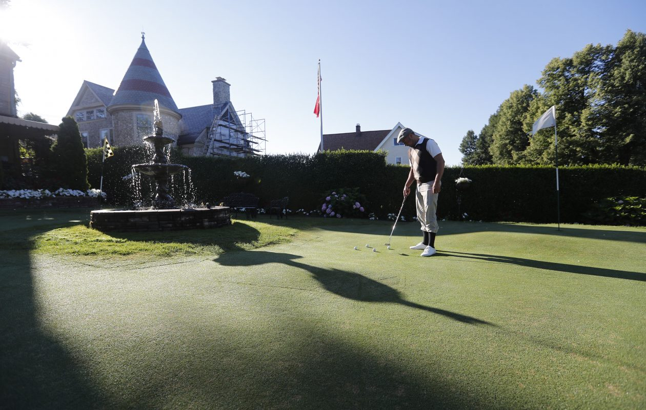 Jose A. Palma, Jr, putts a golf ball on his own private putting green on his Busti Avenue front lawn. (Mark Mulville/Buffalo News)