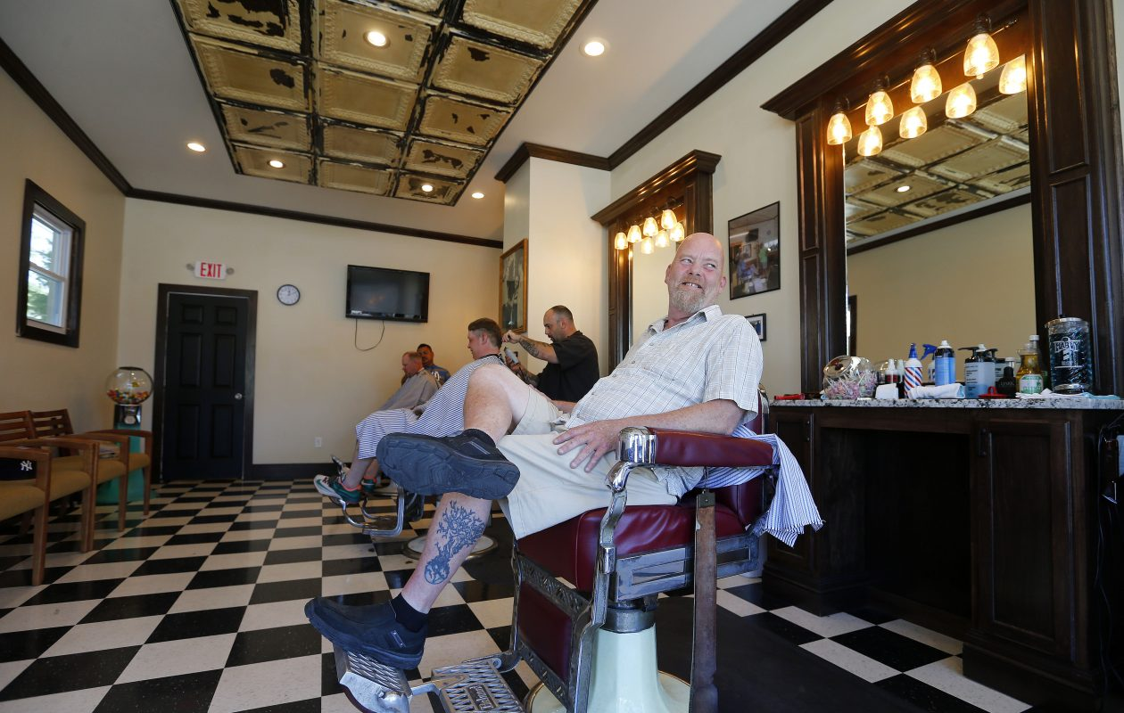 Dan Callahan, right, is the owner of Bob's Barber Shop, one of the businesses in the 100-year-old building newly renovated by Hook and Ladder Development on Seneca Street.  (Mark Mulville/Buffalo News)