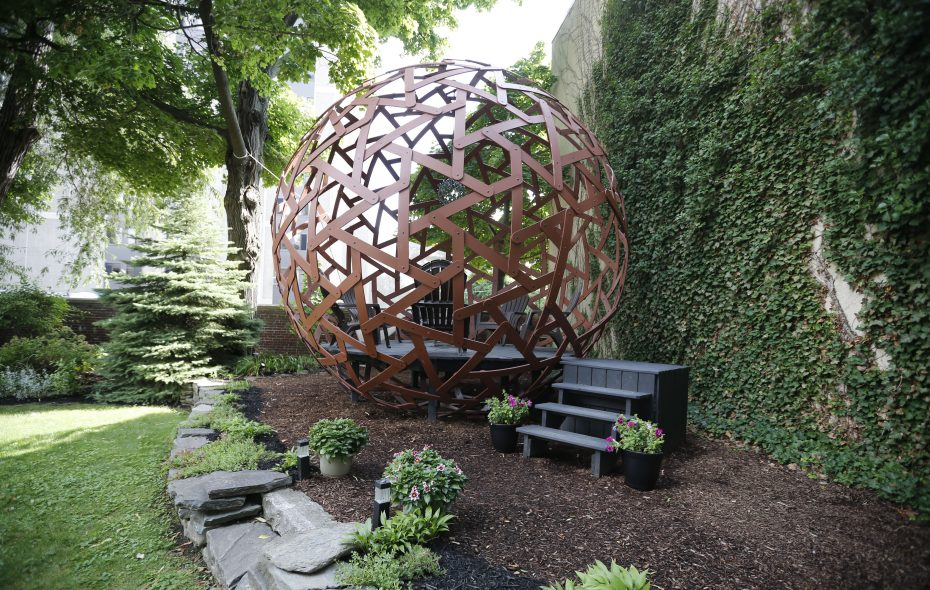 The garden of Tony and Julia Favorito on Linwood Avenue features a sphere with a deck inside. (Derek Gee/Buffalo News)