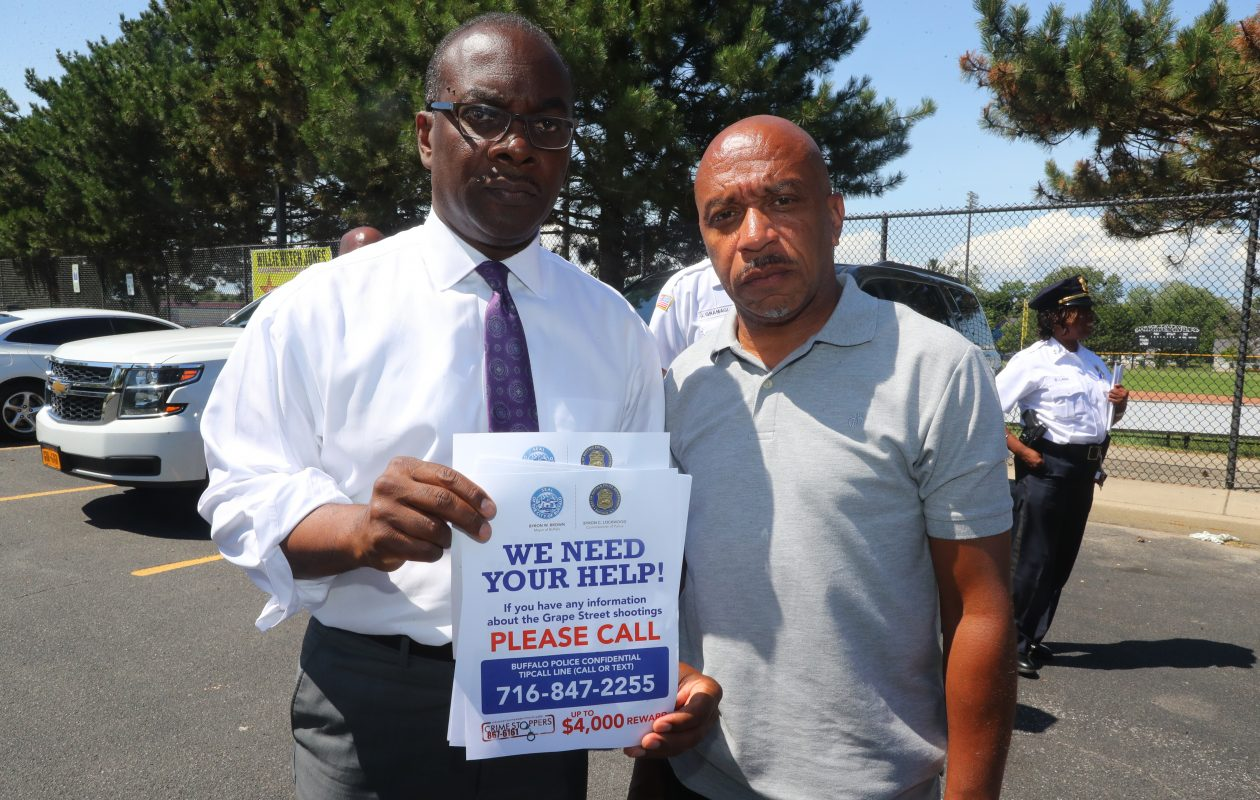 Council President Darius Pridgen represents the Ellicott District,right,  and Mayor Byron Brown  distributed flyers looking for help and a meeting tomorrow after a  shooting Thursday night at the same house on Grape Street where four people were shot July 2, leaving a grandmother and her grandson dead has now left a two men 23 and 24 years old wounded and in the hospital after they were shot last night  at Grape Street, in Buffalo, N.Y., on Friday, July 27, 2018.  (John Hickey/Buffalo News)