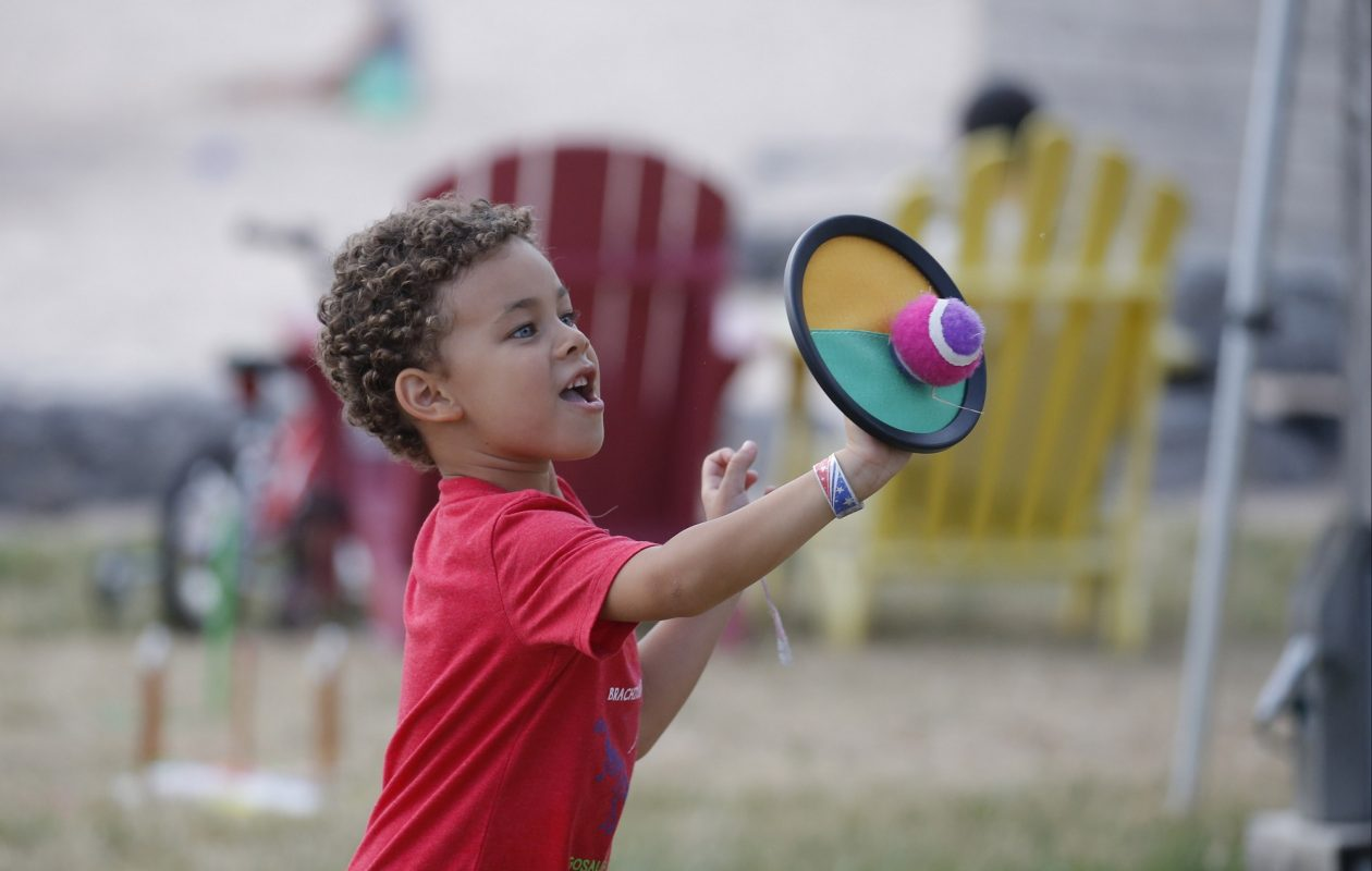 Isaiah Winiarski, 5, of Buffalo catches a fuzzy ball with a hook and loop material disc at a  Sow Fit Buffalo Kids Get Moving fitness night alongside the 'beach' at Canalside. Kids Get Moving starts at 6 p.m. Mondays and Fridays through August, except Aug. 3 and 17. (Robert Kirkham/Buffalo News)