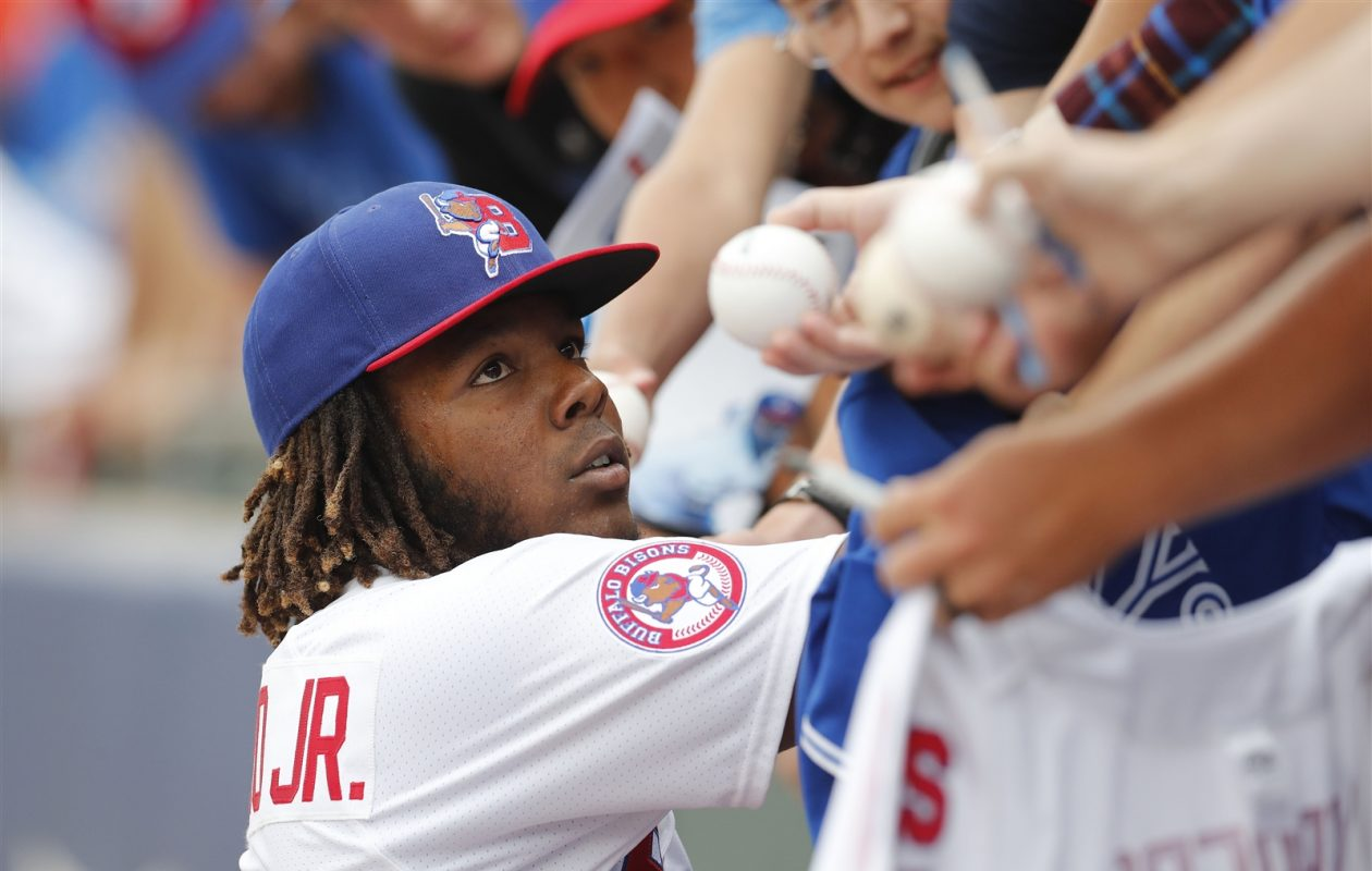 Vladimir Guerrero Jr. signs some autographs before Tuesday's game. (Mark Mulville/Buffalo News)