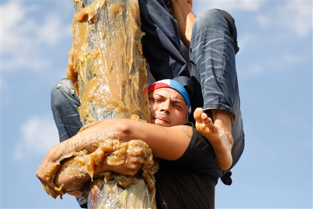 Teams of competitors attempt to reach the top of a 30-foot telephone pole covered in thick grease in the signature event at the 49th annual Grease Pole Festival on Sunday, July 22, 2018.