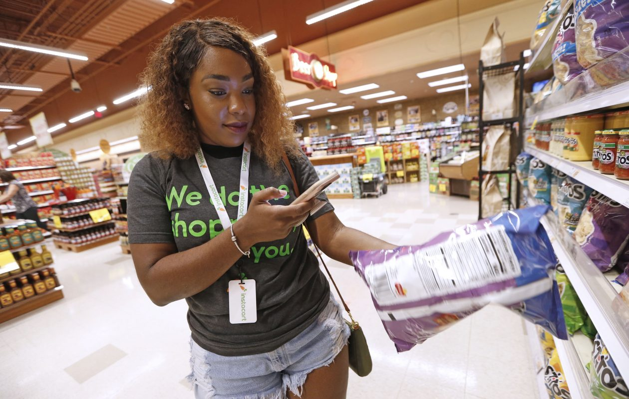 Professional shopper Brianna Johnson of Buffalo uses her smartphone and the app to shop and scan for a customer's order at the Wegmans location on Alberta Drive in Amherst.  (Robert Kirkham/Buffalo News)