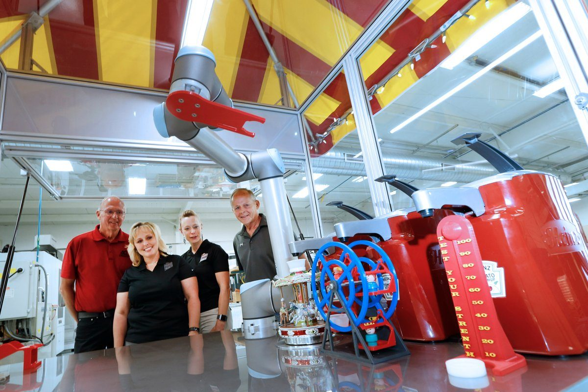 Inventors Tony (left) and Jim Staub (right) look on with Erie County Fair CEO Jessica Underberg (left) and competitive exhibits manager Paula Smith (right) as 'Molly the Ketchup Robot' gets to work. (Robert Kirkham/Buffalo News)