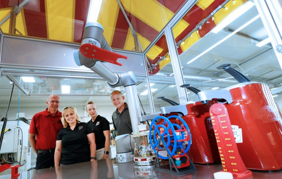 """Inventors Tony (left) and Jim Staub (right) look on with Erie County Fair CEO Jessica Underberg (left) and competitive exhibits manager Paula Smith (right) as """"Molly the Ketchup Robot"""" gets to work. (Robert Kirkham/Buffalo News)"""