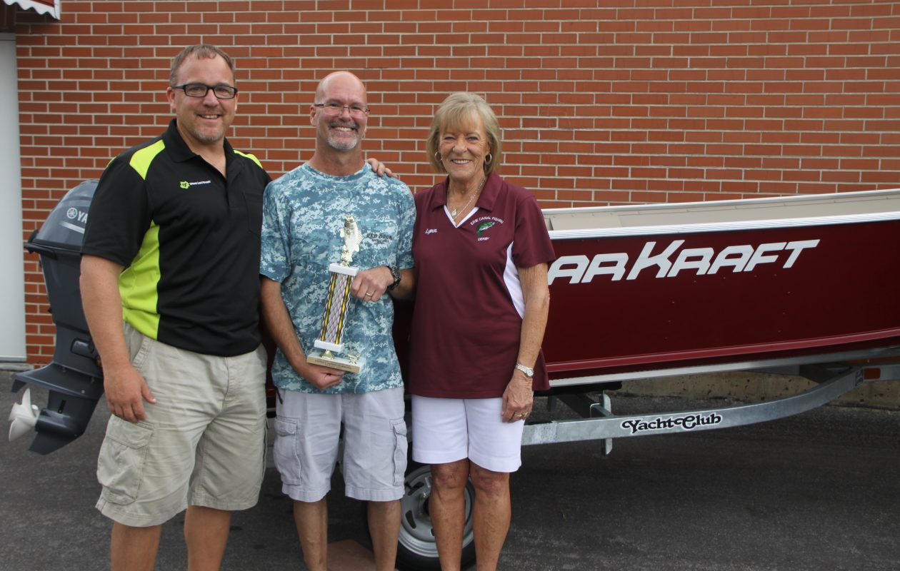 In the drawing for the Grand Prize in the Adult Division, Lee Hathaway, center, was holding the Queen of Hearts ... to win a 16-foot Polar Kraft boat, motor and trailer. Also pictured are Lynn (right) and Brandon Harrington.