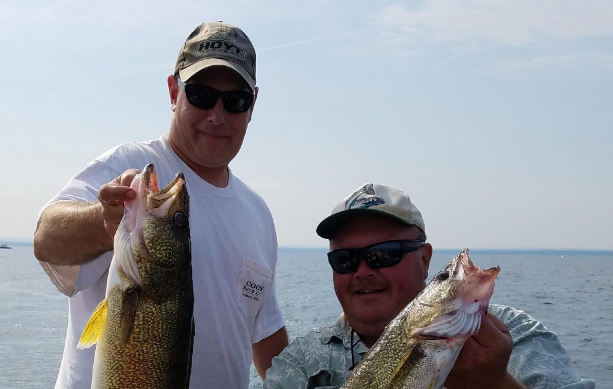 Randy Tyrrell of North Tonawanda and Chad Beyer (left) show off a couple of chunky Lake Erie walleye they caught off Buffalo in July. (Buffalo News file photo)