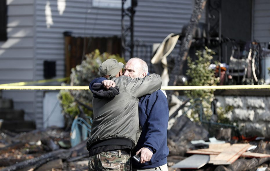 Joseph Conti hugs his neighbor in front of his home on Benzinger Street in Buffalo on Monday, Jan. 29, 2018. The early morning fire took the life of Conti's 7-year-old son. (Mark Mulville/Buffalo News)