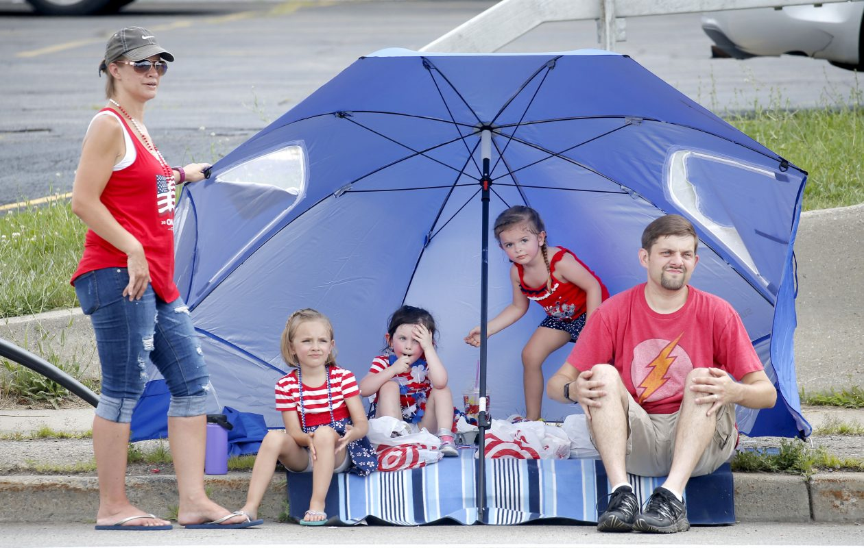 July Fourth was the hottest Fourth of July on record in Western New York.  Here, Brian and Janette Dassero set up their beach umbrella for their two daughters, Abigail, 5, left, and Emily, 4, right, and their friend Penelope Szymborski, 3, as they watched  Cheektowaga's Independence Day Parade along Harlem Road. (Robert Kirkham/Buffalo News)