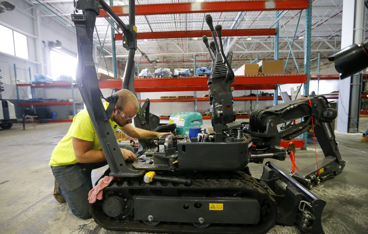 Ryan Ball of newly formed Buffalo company Viridi Parente, works on converting a one-ton excavator to all electric. (Mark Mulville/Buffalo News)