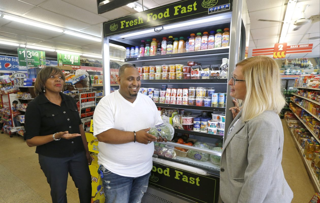 Trade Fair Food Market owner Adel Munassar, center, discusses healthy food options in front of one of his 'Fresh Fast Food' refrigerated cases with Sheila Bass and Annie Todd at his store on East Delavan Avenue in Buffalo.  (Robert Kirkham/Buffalo News)
