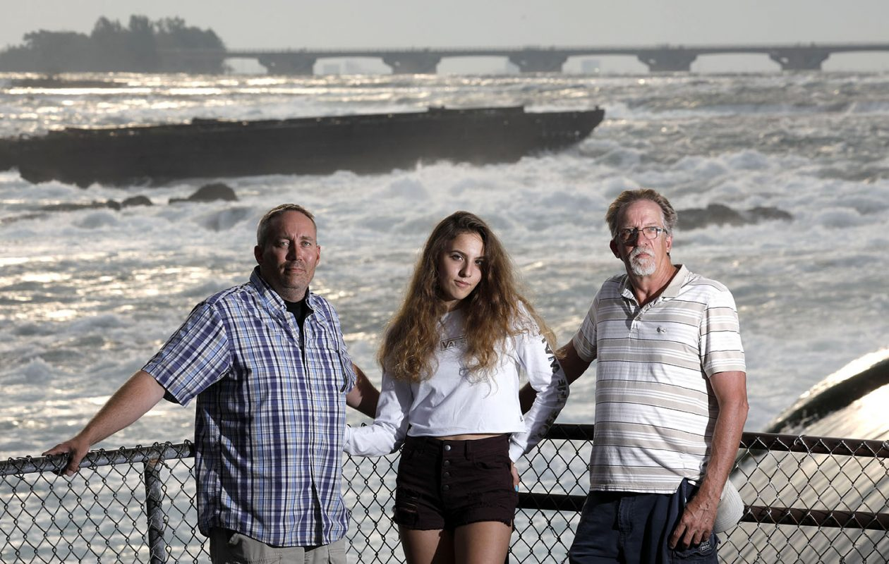 With the scow that ran aground 100 years ago behind them, descendants of Red Hill Sr. gather in Niagara Falls, Ont.: From left, Kip Finn, a great-grandson; Danni Hill, a great-granddaughter; and her father, Dan Hill, a grandson. (Derek Gee/Buffalo News)