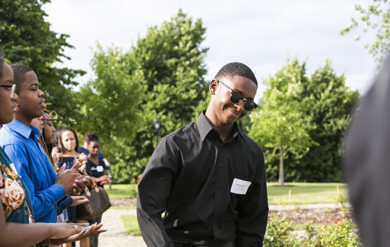 Eight Buffalo Promise Neighborhood students receive scholarships and celebrate at Delaware Park's Marcy Casino in Buffalo on Wednesday. Carlo Gordon Jr., one of the students getting scholarships, walks up to the stage. (Shuran Huang/Buffalo News)