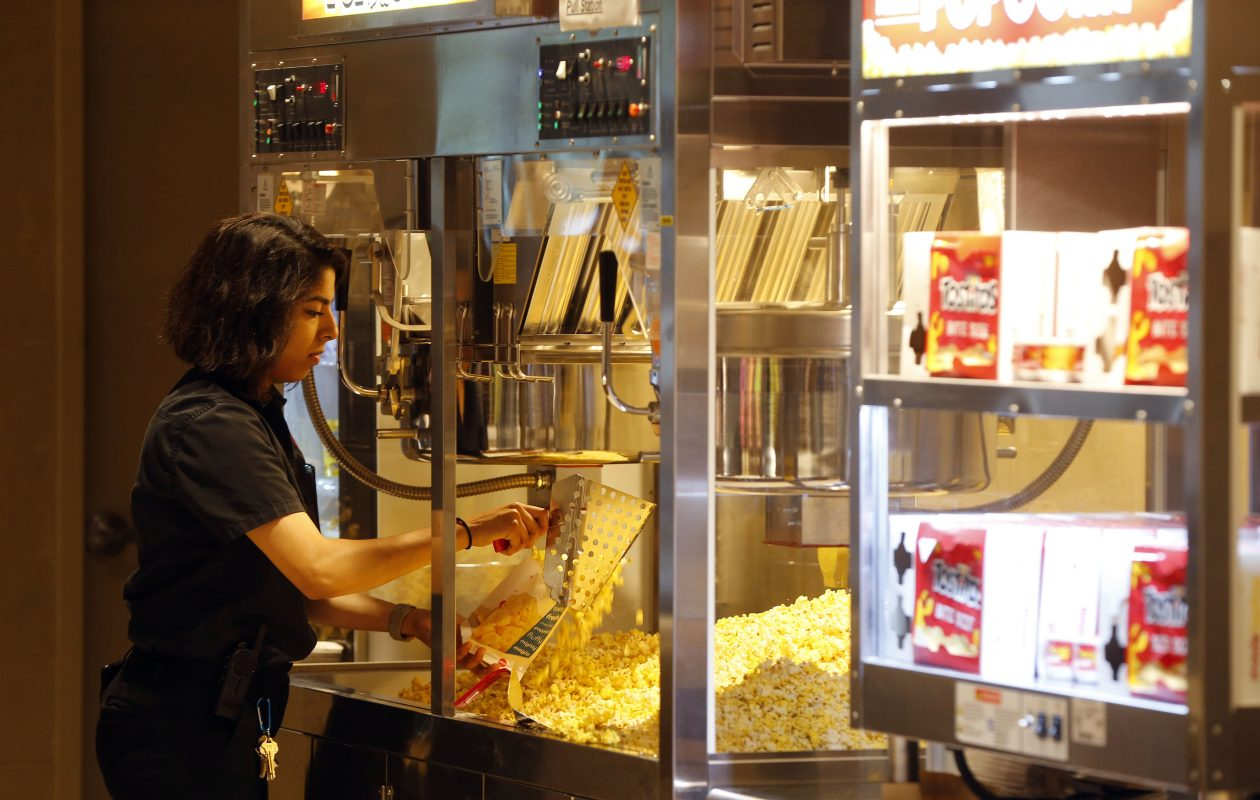Noel Abdallah fills bags of popcorn in the new AMC Market Arcade 8 Movie Theatre on Main Street.   (Mark Mulville/Buffalo News)