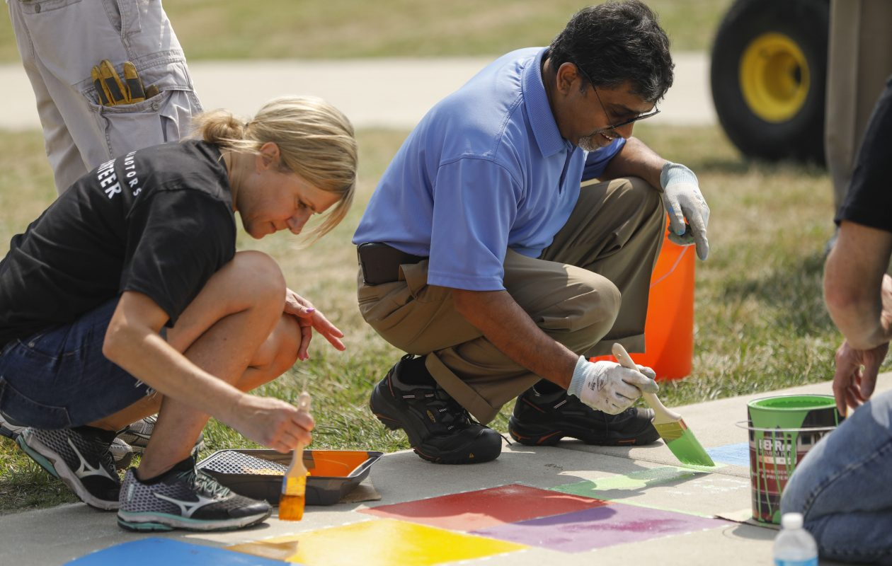 Gina Moell of the GM Tonawanda Engine Plant, left, and Plant Director Ram Ramanujam, paint a hopscotch grid on the sidewalk while helping to create a new 'Born Learning Trail,' a series of 10 signs and corresponding activities for children on the sidewalk around the playground at Buffalo Outer Harbor State Park as part of the United Way Day of Caring. (Derek Gee/Buffalo News)