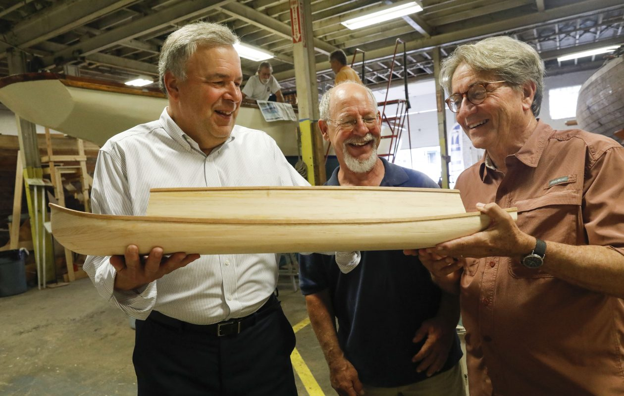 Dave Rogers, left, looks on as master boat builder Roger Allen, center, and John Montague, founder and director emeritus of the Buffalo Maritime Center, use an unfinished model of a packet boat to describe the plan to build a 73-foot replica to be displayed at Canalside on Aug. 21, 2018. (Derek Gee/News file photo)