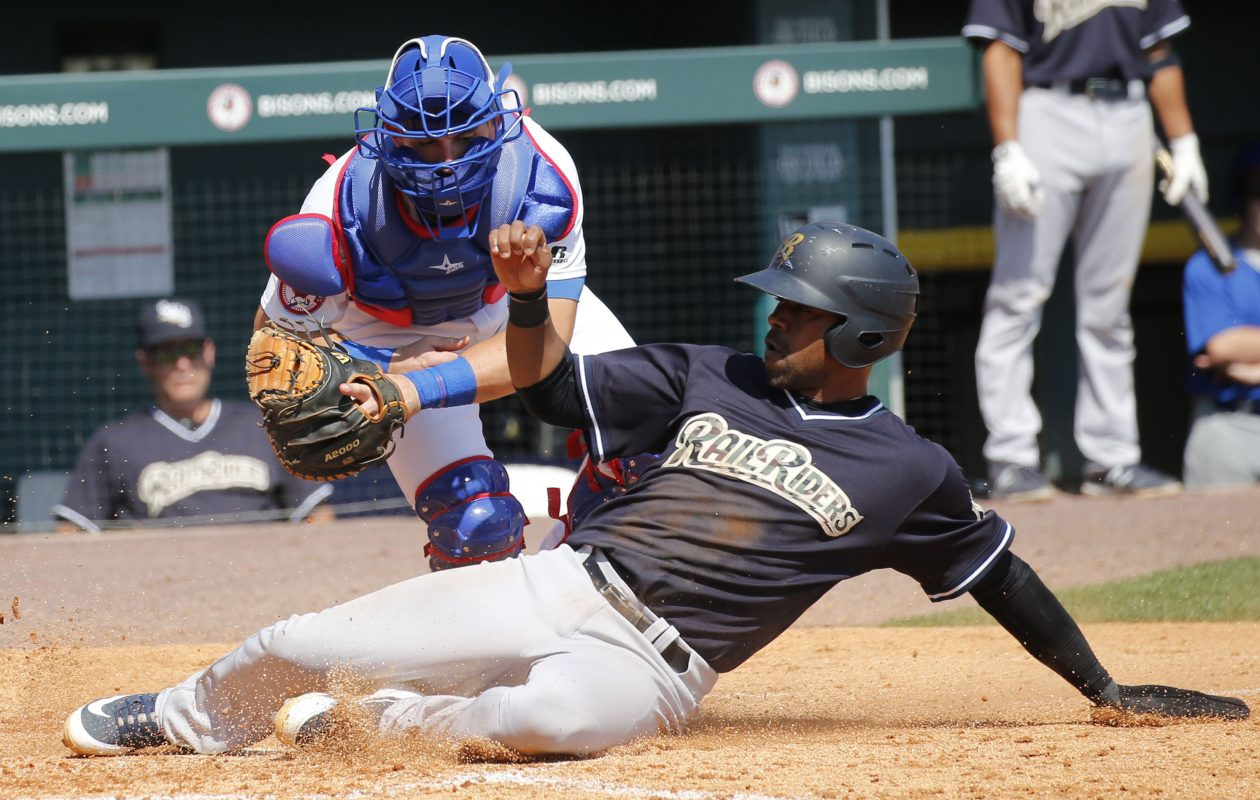 Scranton Wilkes‑Barre RailRiders baserunner Wilkin Castillo slides into home for a run as Buffalo Bisons catcher Alberto Mineo can't hang on to the throw. (Derek Gee/Buffalo News)