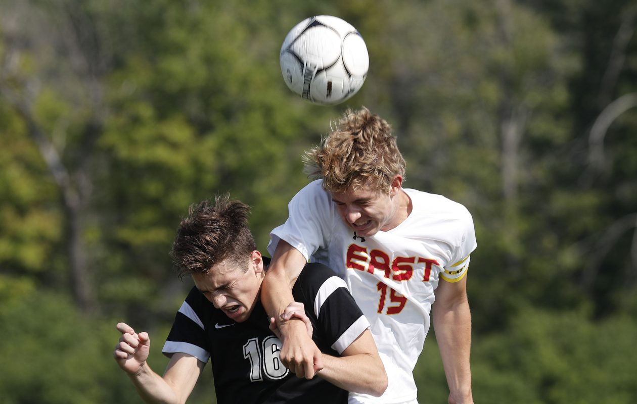 Williamsville East's Ben Woolingham hits the ball away from Lancaster's Adam Kolis during the teams' Coaches Kicking Cancer game at Sweet Home High School. (Mark Mulville/Buffalo News)