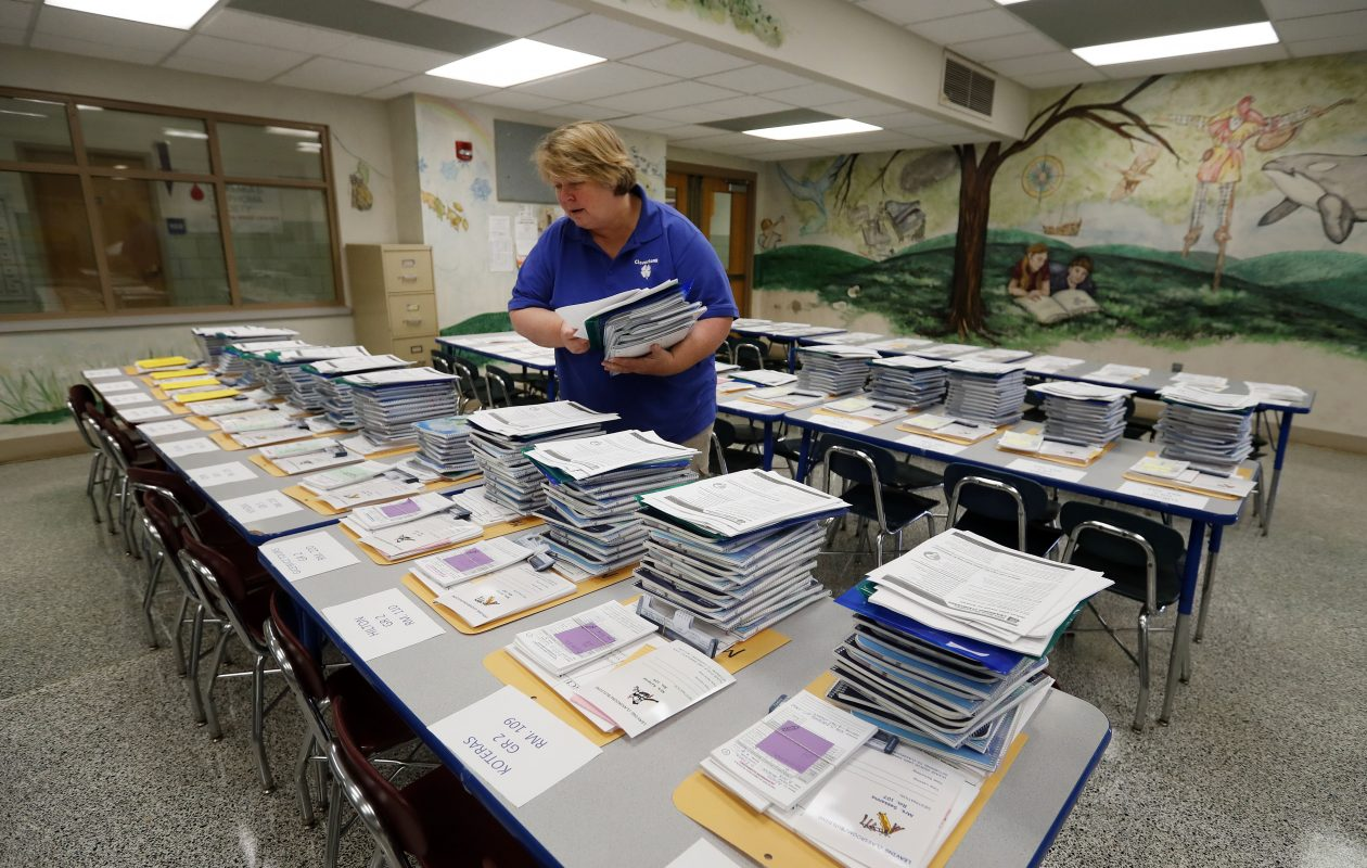 School secretary Mary Gates stacks first-day materials in the cafeteria as teachers and staff get ready for the new school year at Cloverbank Elementary in Hamburg. (Mark Mulville/Buffalo News)