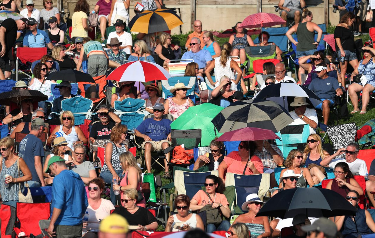 The crowd at Artpark shields itself from the warm sun prior to Tuesday's final Tuesday In The Park concert, which featured the B-52s. (Sharon Cantillon/Buffalo News)