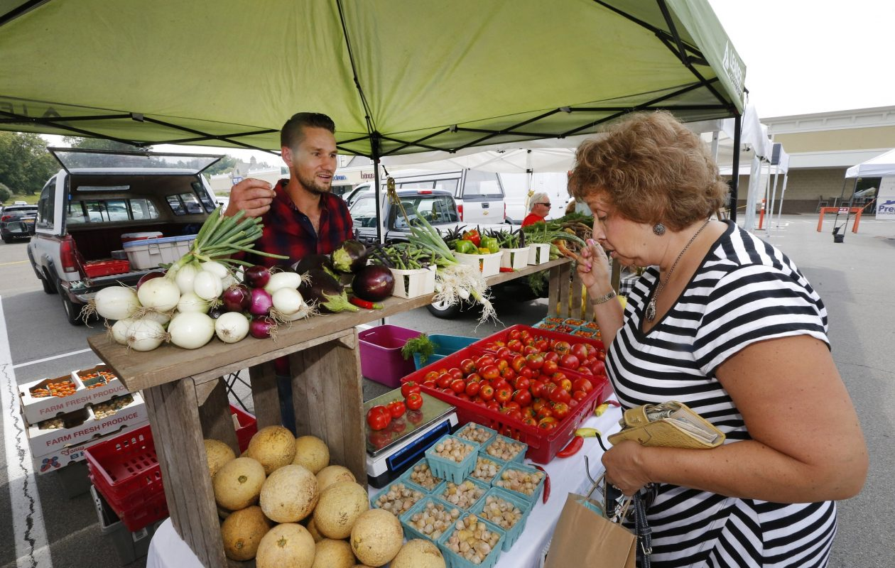 Chris Leipler waits on Mary Beth Jones, of Hamburg, last Thursday during the Orchard Park Farmers and Artisans Market, outside Orchard Fresh grocery store. Leipler and his wife, Beth, started a farm earlier this year in nearby West Falls.  (Robert Kirkham/Buffalo News)