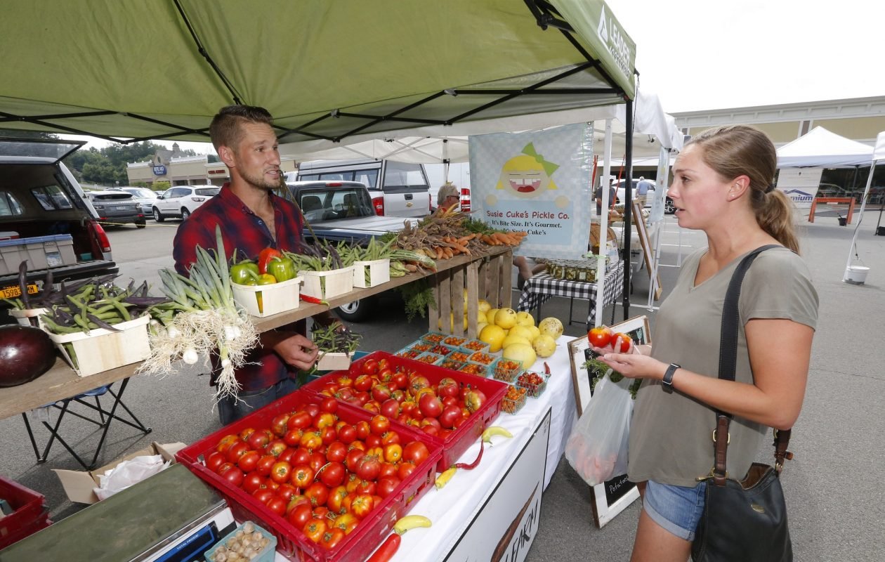 Tioga Valley Farm co-owner Chris Leipler waits on Catherine Wurstner, of Orchard Park, last week at the Orchard Park Farmers and Artisans Market. Leipler and his wife, Beth, started their farm this year. (Robert Kirkham/Buffalo News)