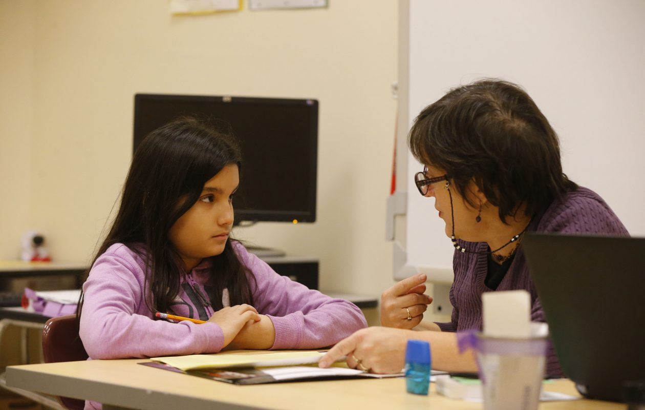 Giuca Bauman works with Griselirys Reyes Nieves at Herman Badillo Bilingual Academy in January. (Mark Mulville/Buffalo News)