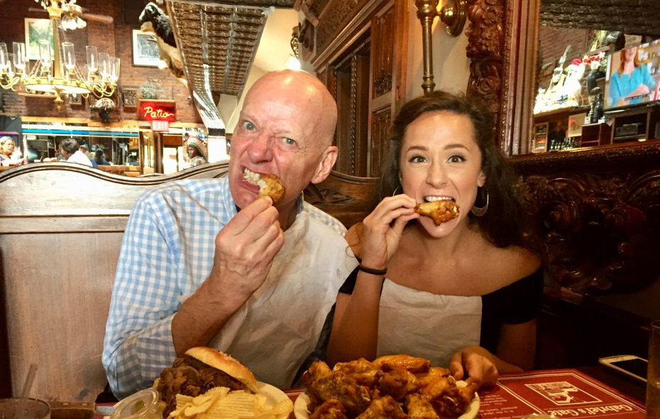 """Jonathan Weir and Lissa deGuzman, Jafar and Jasmine in """"Aladdin,"""" dive into a plate of chicken wings at Gabriel's Gate. (Francesca Bond/The Buffalo News)"""