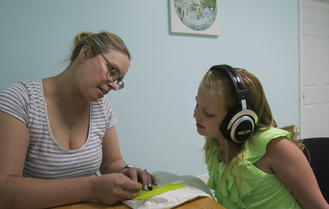 "'""Your brain can grow and change – and you've got to challenge it,' says Sarah Smith, owner of Kinesthetic Listening Center of Western New York in East Aurora. She is pictured helping Olivia Greiner during a recent craft session. (Shuran Huang/Buffalo News)"