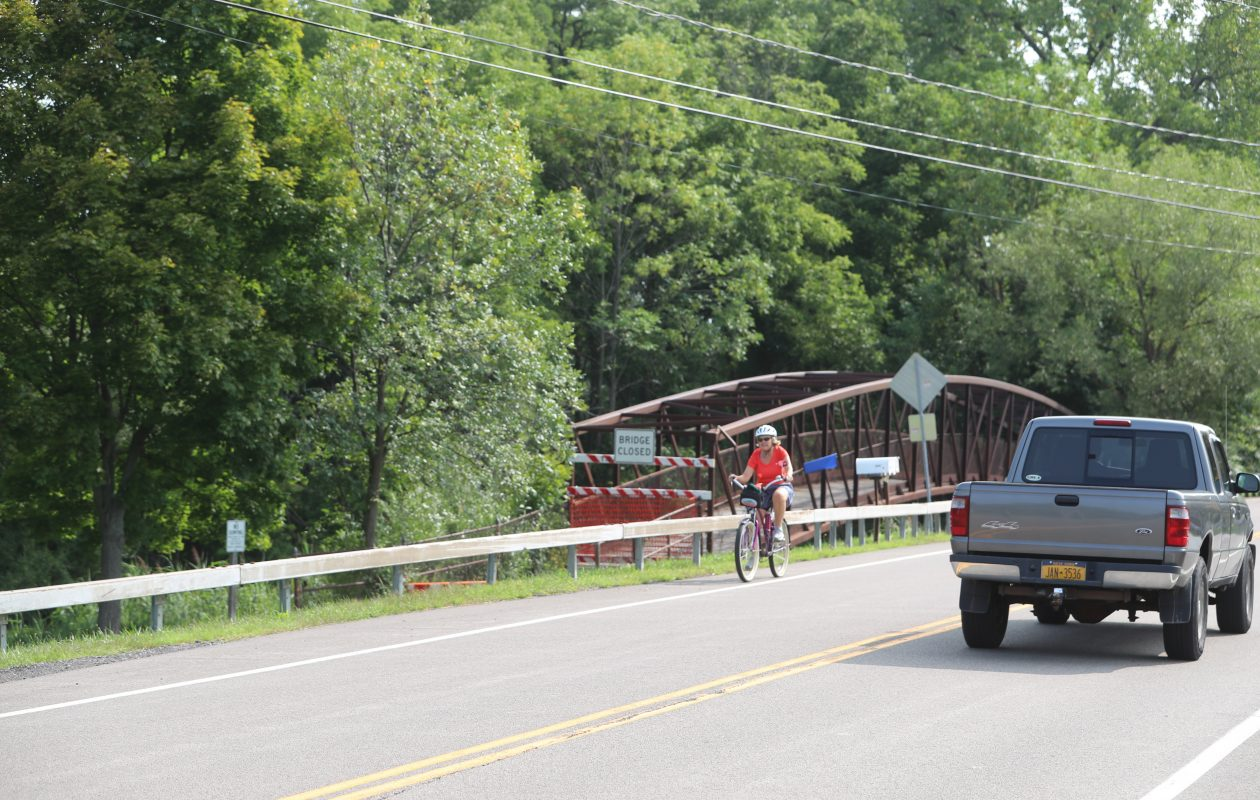 The Town of Amherst last week shut down the pedestrian bridge on the Erie Canal Trailway over Ransom Creek due to safety concerns. This bicyclist is riding on the shoulder of the adjacent Tonawanda Creek Road bridge, against the recommendation of town officials. (John Hickey/Buffalo News)