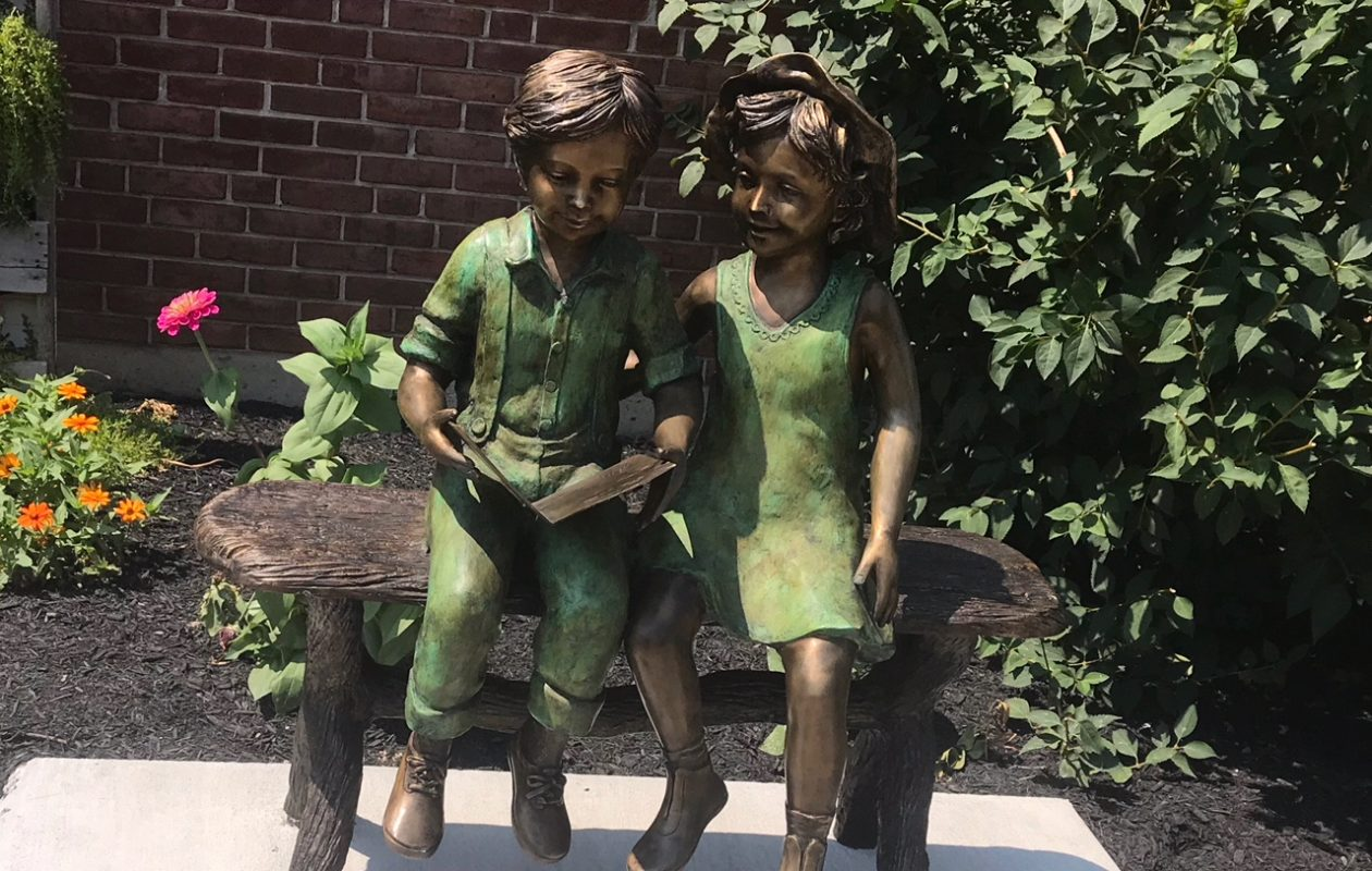 Nick and Marcia Roth of Williamsville have donated this cast bronze statue, 'Best Friends,' to the village library. It is on display outside the Williamsville Library along Main Street. (Photo courtesy of the Village of Williamsville)