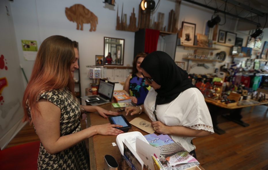 Andrea Dacey, left, owner of Buffalo Adore store, in the Market Arcade, helps  Lisa Rivera check out as they shop on their lunch break in 2016.  (John Hickey/News file photo)