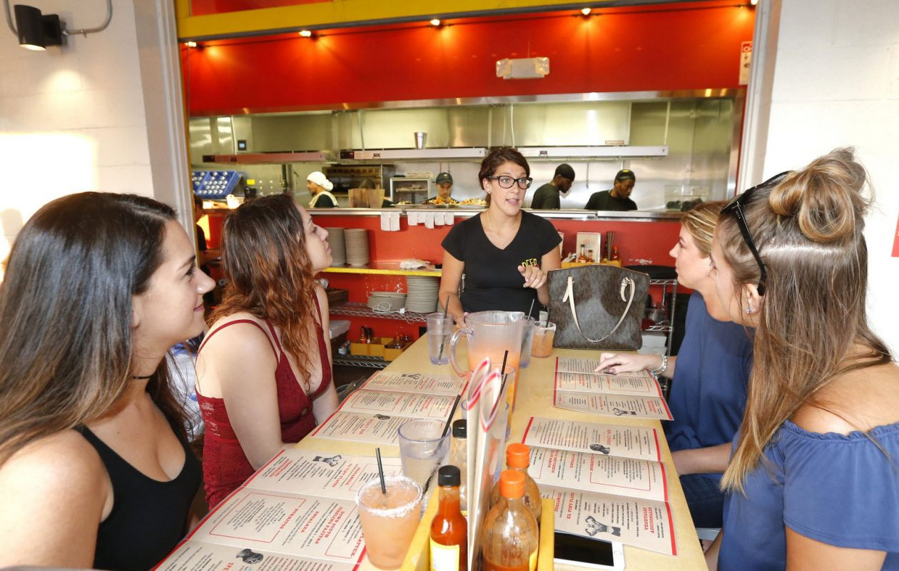Server Lindsey Abbott, center, explains Taco Tuesday to Deep South Taco customers. (Robert Kirkham/Buffalo News)