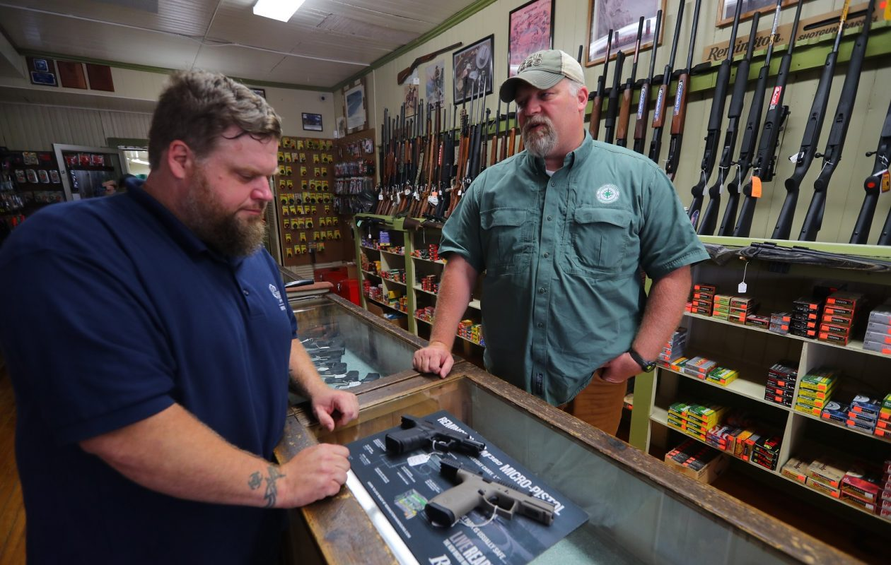 The number of Erie County residents gaining their pistol permits and buying/registering handguns is on the rise. Firearms trainer Jim Emmick, left, and Adam Henrich, a certified gunsmith and owner of John Henrich Co.,, a gun shop in Eden, look at hand guns, in the shop.    (John Hickey/Buffalo News)