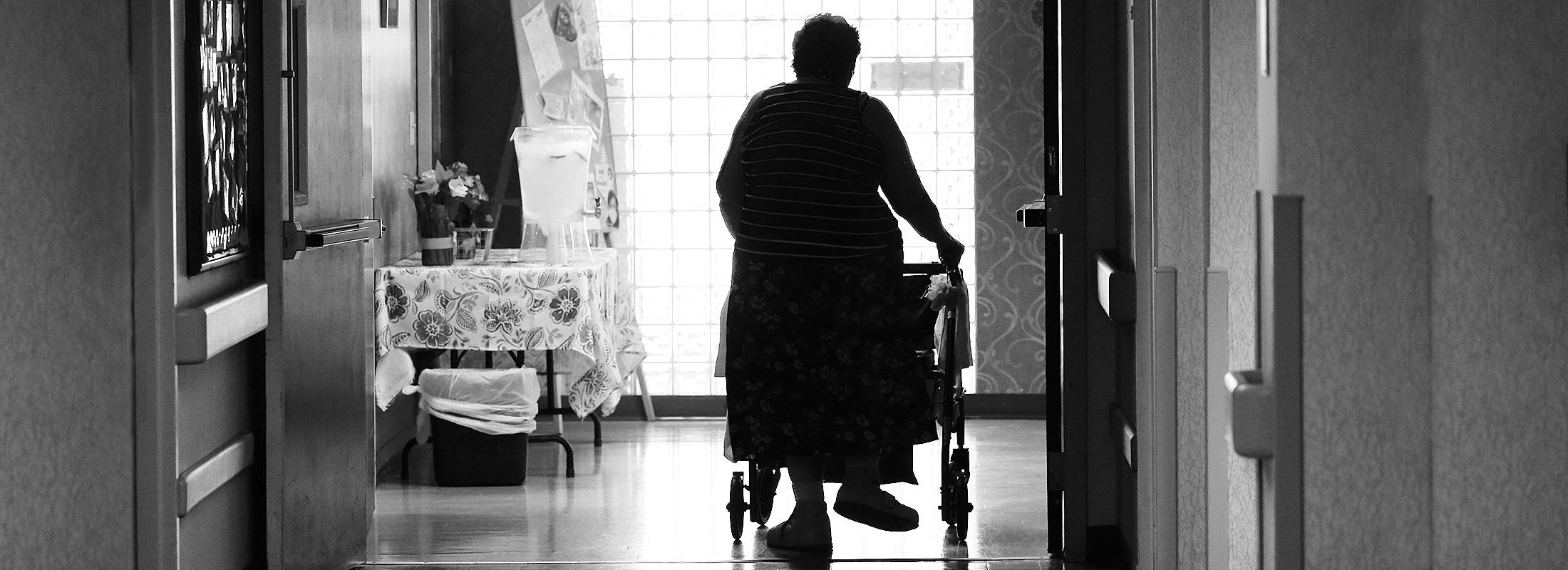 A resident walks down a hallway at Emerald South Nursing and Rehabilitation Center. on Delaware Avenue. (Robert Kirkham/Buffalo News)